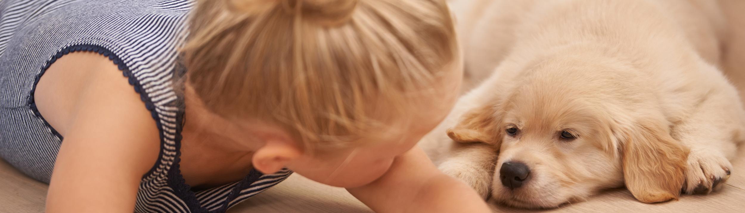 Junger Hund und kleines Mädchen liegen am Boden. Fussbodenheizungen machen Ihren Fussboden gemütlich.
