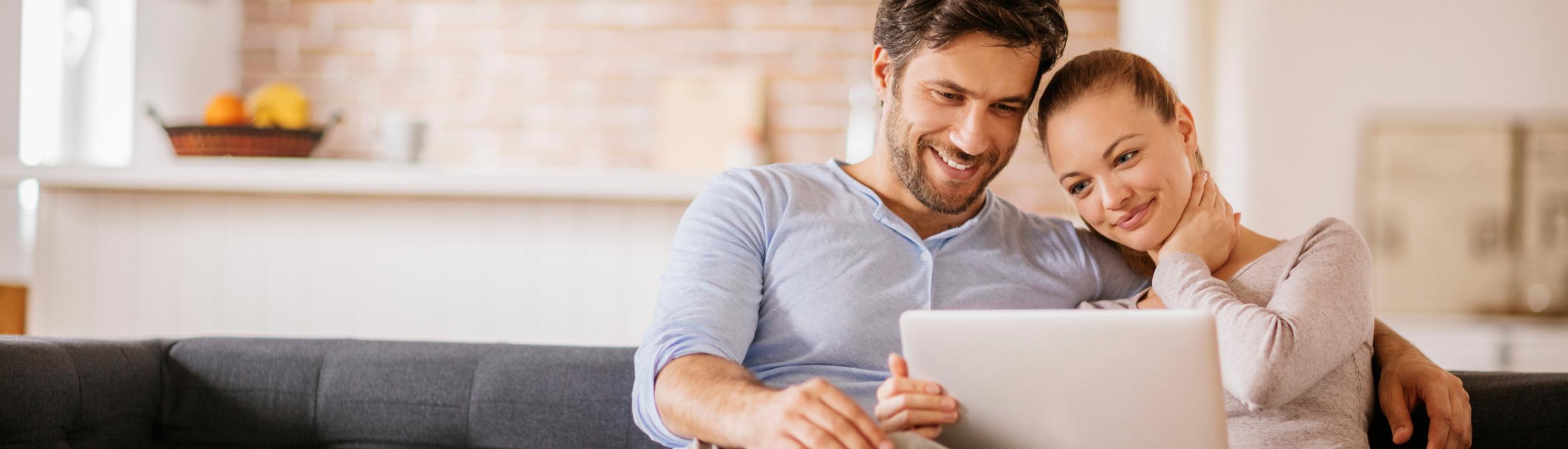 Ein Paar schaut auf den Laptop und lächelt.