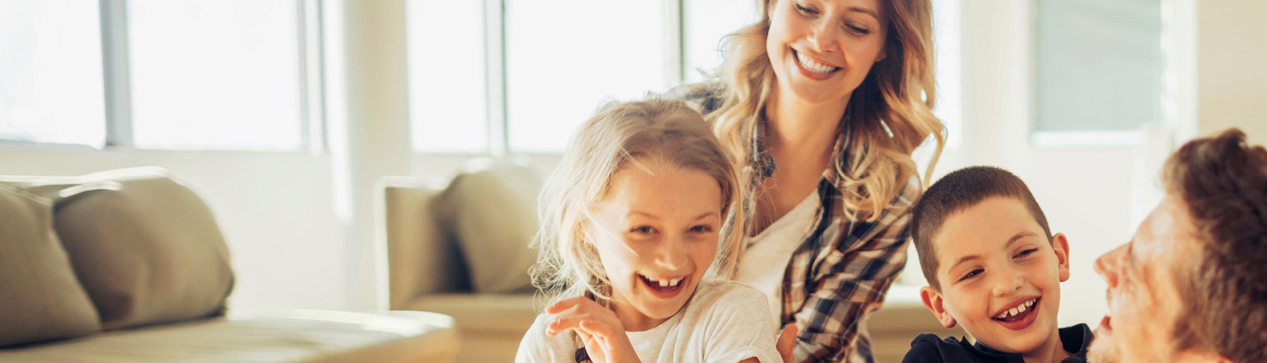 Eine junge Familie lacht mit Ihren Kindern. Dank Heizungen der Firma Gerber & Güntlisberger AG, gibt es keine Sorgen.
