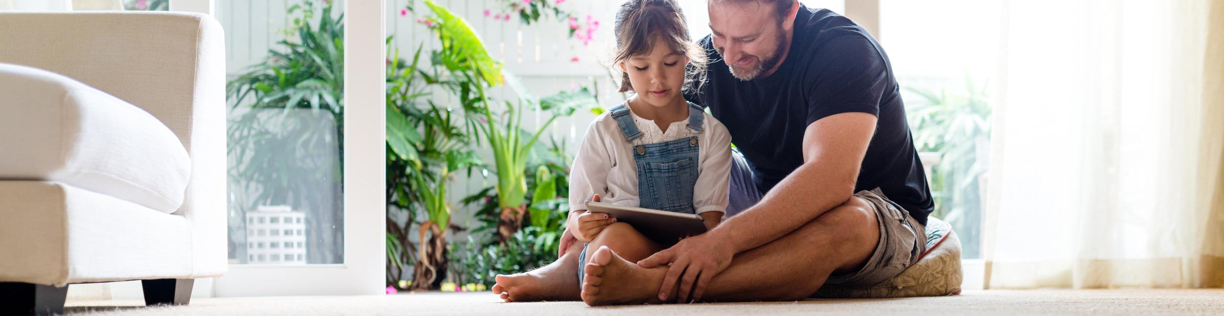 Vater und Tochter entspannen auf dem Fussboden. Dank Fussbodenheizung wird Ihr Fussboden zu einem Entspannungsort.