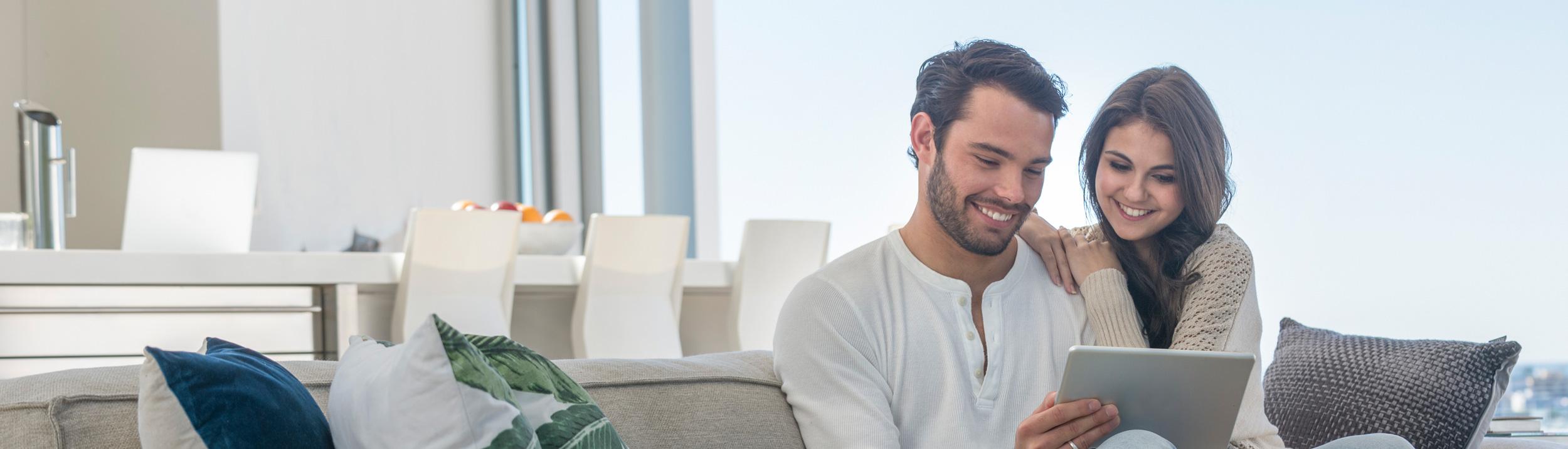 Ein Paar sitzt auf dem Sofa, schaut auf ein Tablett und lächelt. Wohliges Zuhause dank guter Heizung.