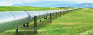 Eine Pipeline für Oelheizungen durch eine grüne Landschaft.