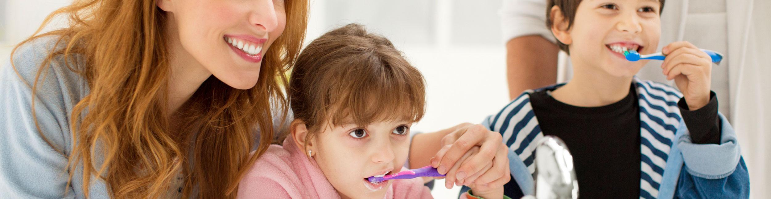Mutter mit zwei Kindern beim Zähneputzen in Ihrem neuen Badezimmer