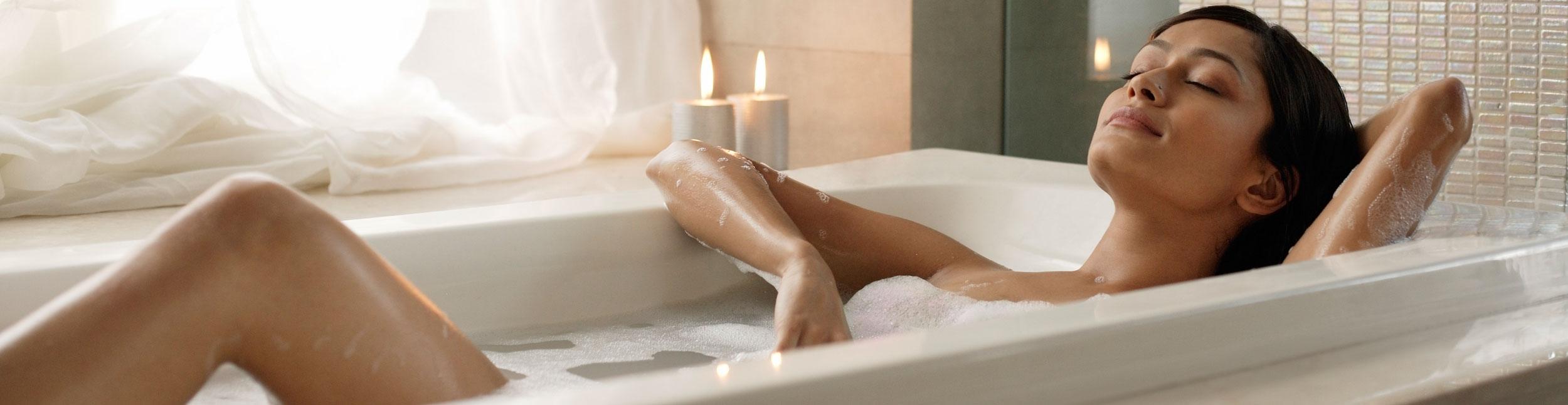 Hübsche Frau entspannt sich in Badewanne mit Kerzen in Ihrem schön sanierten Badezimmer.