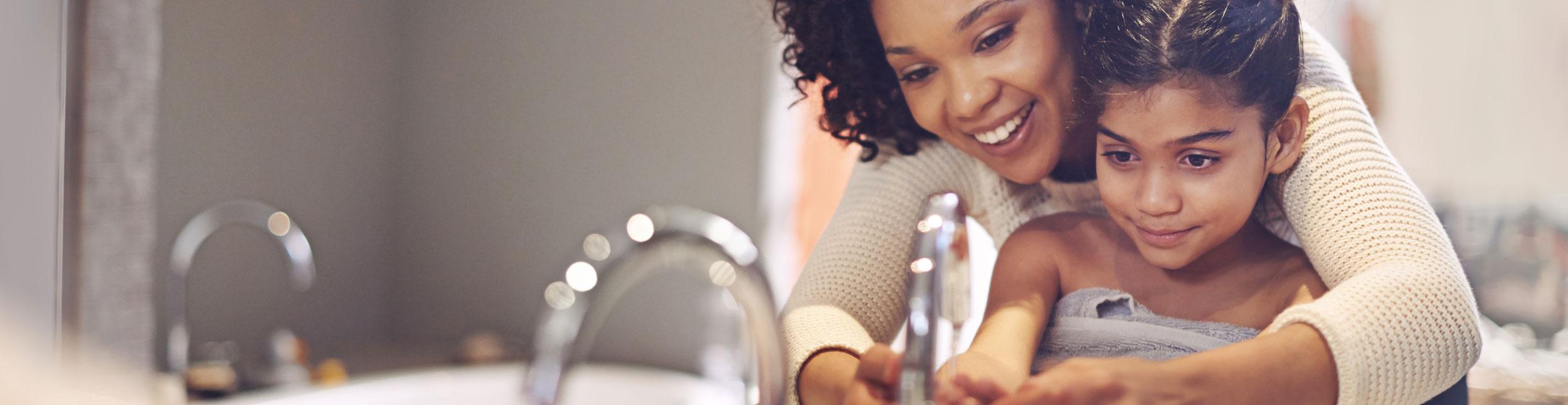 Mutter und kleine Tochter waschen sich die Hände in Ihrem schön sanierten Badezimmer.