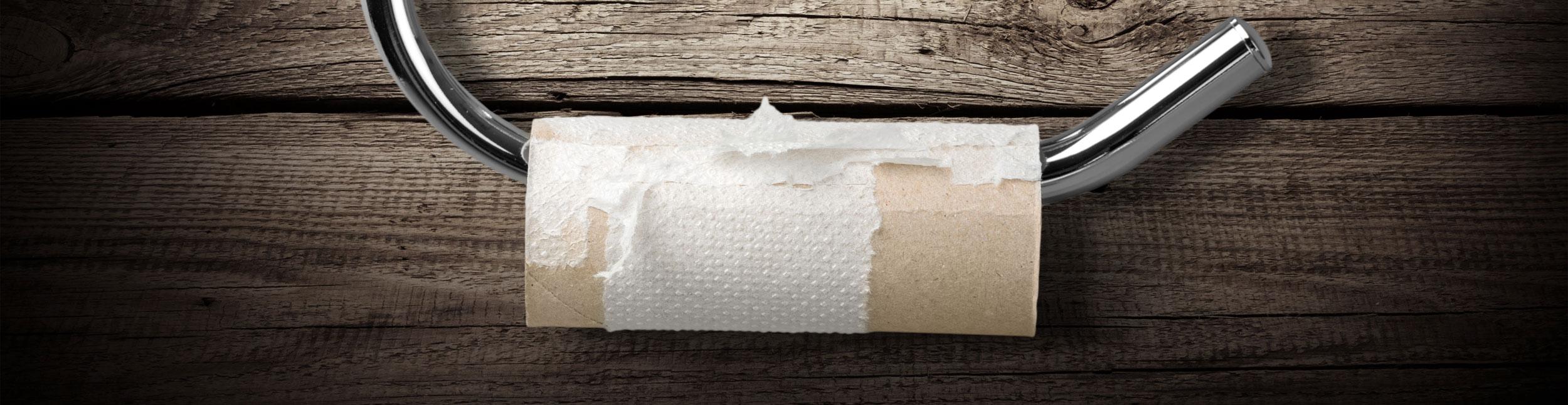 Eine leere Rolle Toilettenpapier hängt im Halter