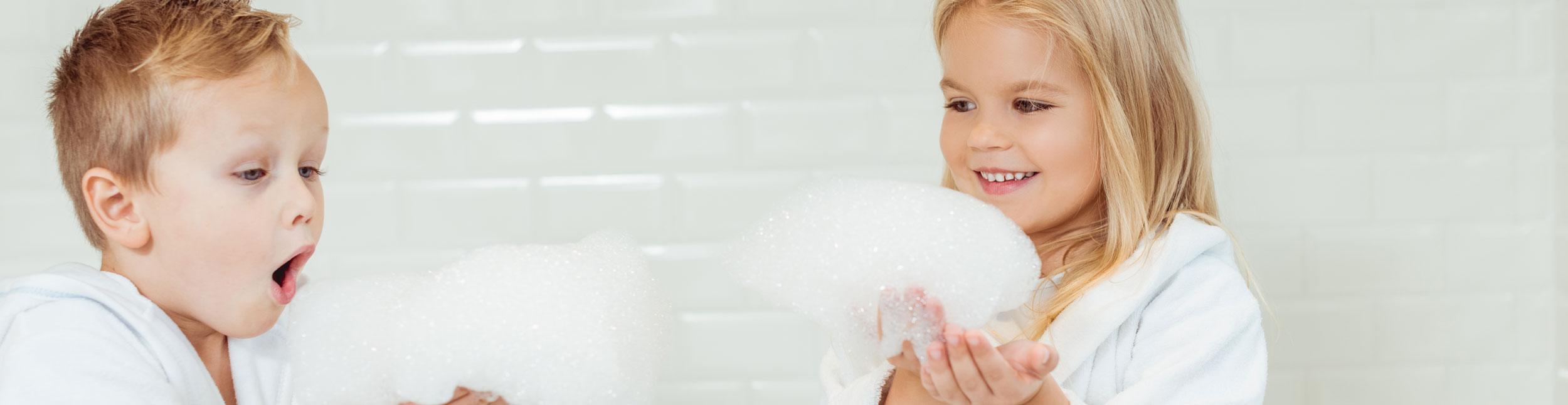 Zwei Kinder spielen mit Schaum im frisch renovierten Badezimmer