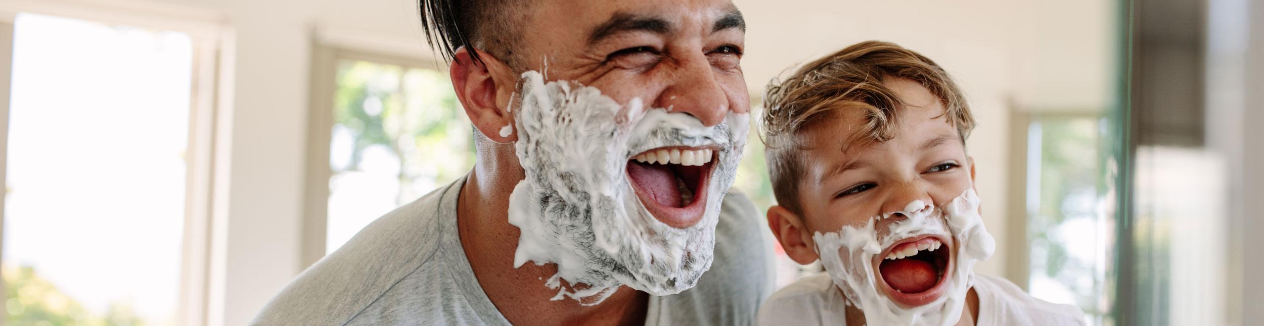 Vater und Sohn mir Rasierschaum im Gesicht lachen in den Spiegel nach Badumbau